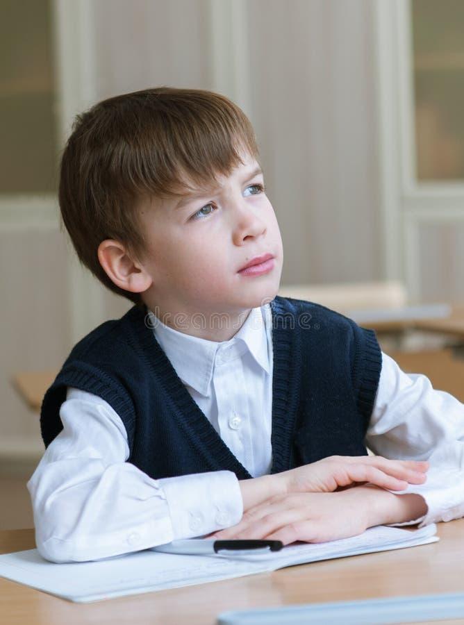 坐在书桌,教室的努力学生 免版税库存图片