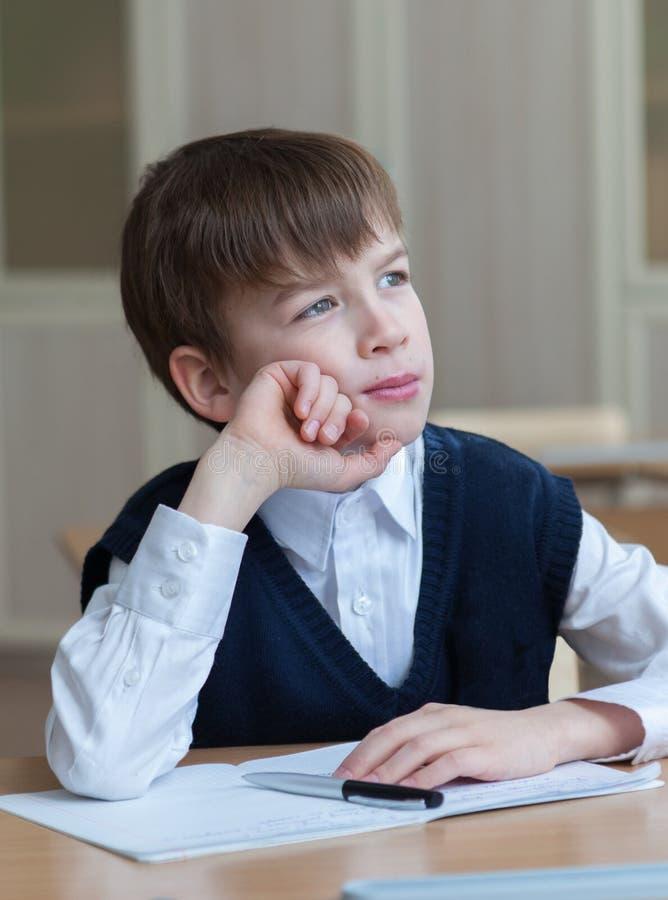 坐在书桌,教室的努力学生 免版税库存照片