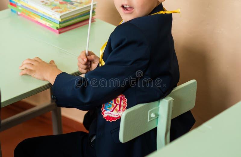 坐在书桌,教室的愉快的男小学生 免版税图库摄影