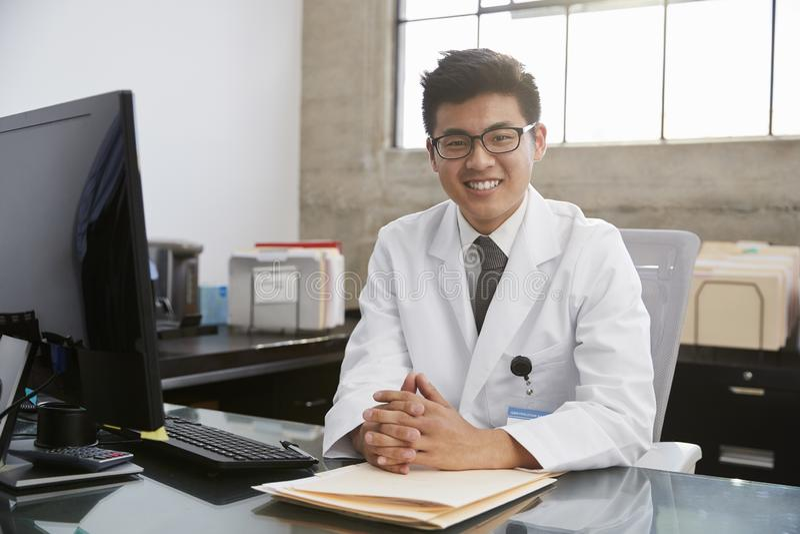 坐在书桌,画象的年轻亚裔男性医生 免版税图库摄影