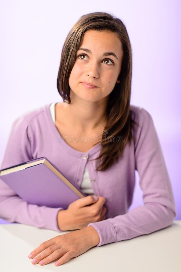 坐在书桌紫色后的想法的学生女孩 库存照片