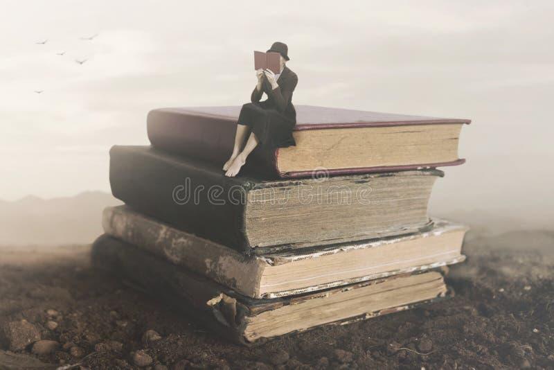 坐在书顶部的妇女读书的超现实的图象 免版税库存图片