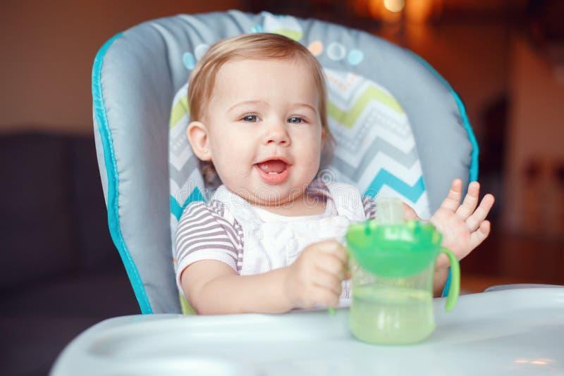 坐在从防溢出的sippy杯子的高脚椅子饮用水的白种人儿童孩子女孩 免版税库存图片