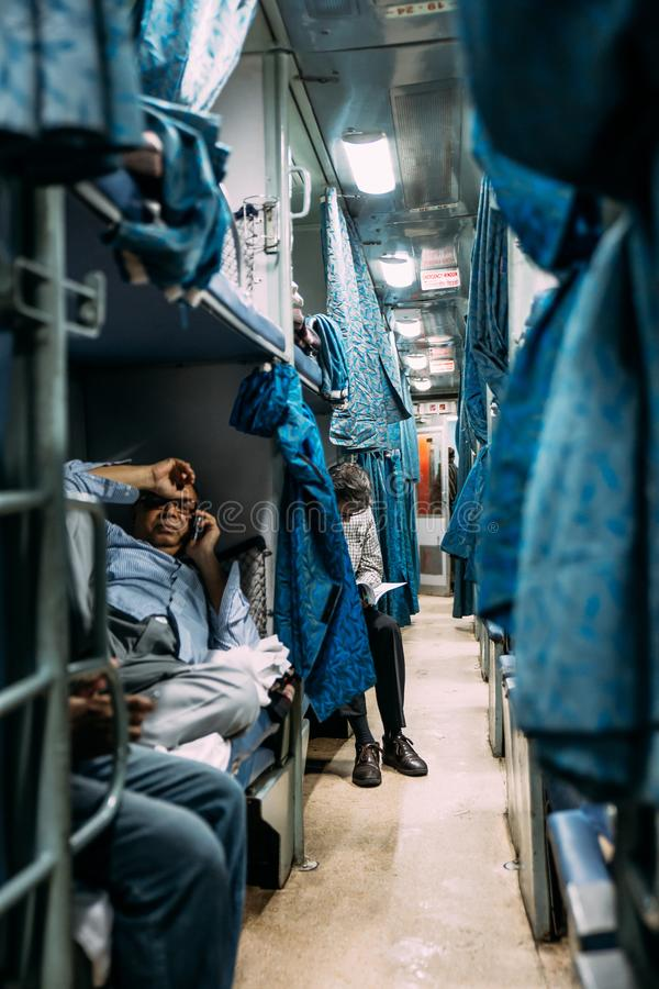 坐在他们的与帷幕的位子的印度人民,当空调移动从豪拉连接点火车站时的睡觉火车 免版税库存照片