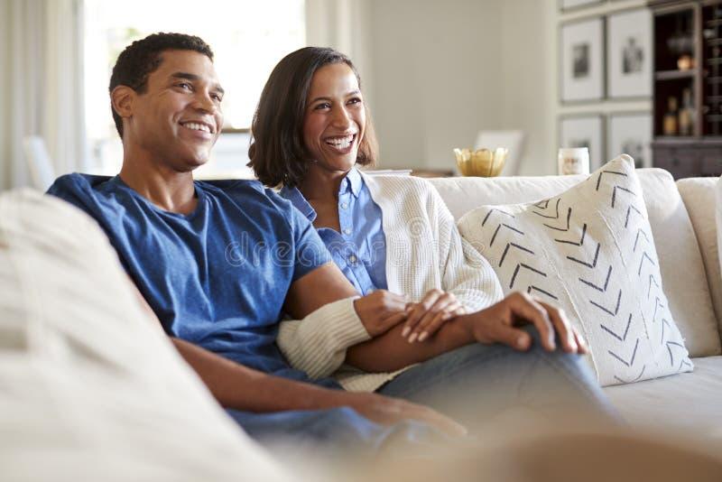 坐在他们的客厅看着电视的沙发和吃玉米花,选择聚焦的愉快的非裔美国人的千福年的夫妇 免版税库存图片