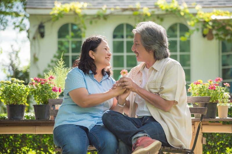 坐在他们的房子和微笑前面的退休的夫妇 库存图片