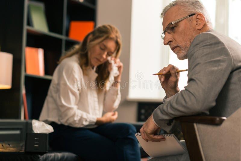 坐在他哭泣的女性患者旁边的心理治疗家 库存图片