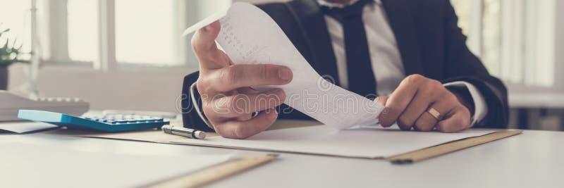 坐在他的书桌工作的财政顾问的宽看法图象 库存照片