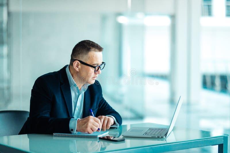 坐在他的在计算机和膝上型计算机前面的工作站的资深财政商人,当做一些文书工作时 库存图片