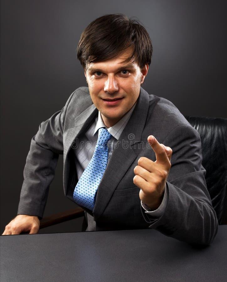坐在他的服务台之后的生意人 免版税库存照片