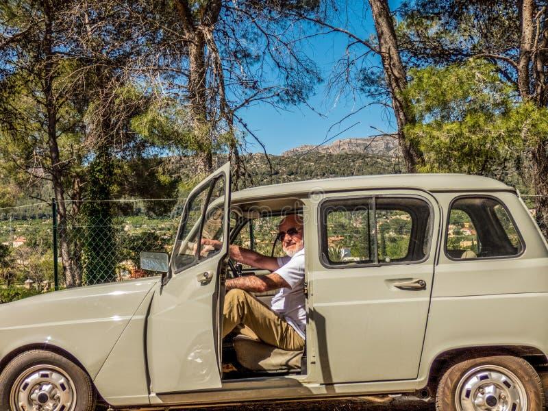 坐在他的汽车的更老的微笑的人在好日子 免版税库存图片