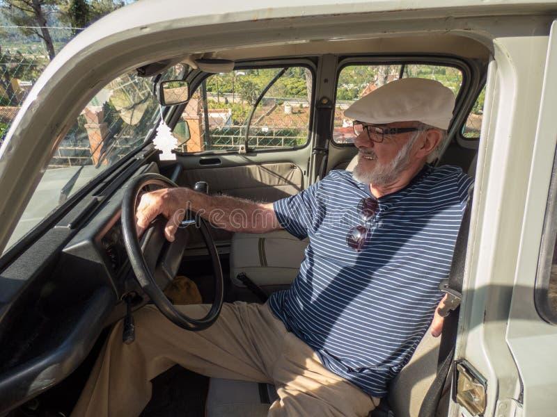 坐在他的汽车的更老的微笑的人在好日子 库存图片