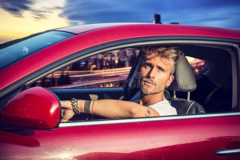 坐在他的汽车的英俊的白肤金发的年轻人 免版税库存照片