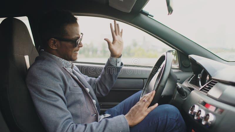 坐在他的汽车里面的翻倒和恼怒的混合的族种商人户外 免版税库存图片