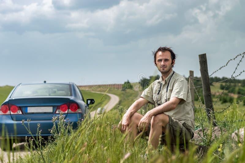 坐在他的蓝色汽车附近的年轻旅客在乡下 免版税图库摄影