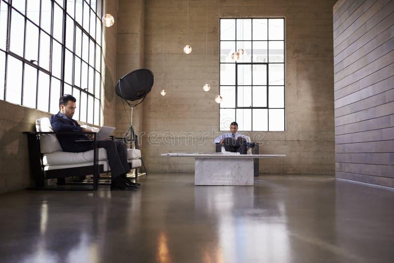 坐在企业大厦的休息室的两个人 库存图片