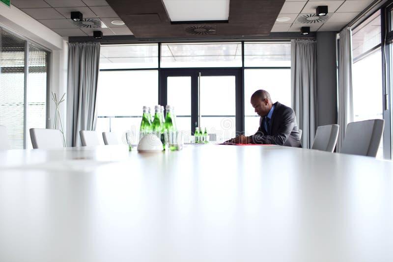 坐在会议桌上的年轻商人侧视图 库存图片