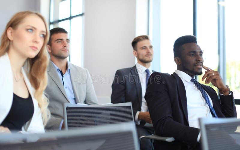 坐在会议的小组商人对讲话,当开业务会议时 免版税库存照片