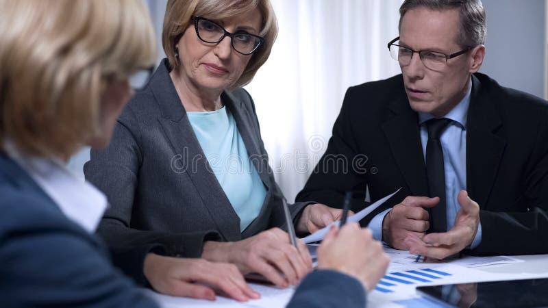 坐在会议的生气同事,不满意对秘书报告  免版税库存图片