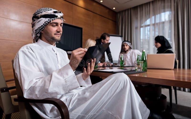 坐在会议的年轻有胡子的人 免版税库存照片