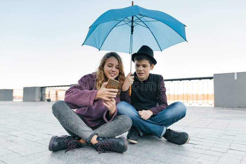 坐在伞下和看智能手机,少年生活方式的微笑的青少年的朋友夫妇在城市 图库摄影