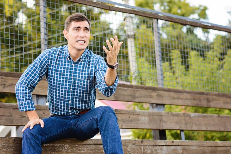 坐在体育场的年轻人观看场面,担心队 情感面孔 复制空间 图库摄影