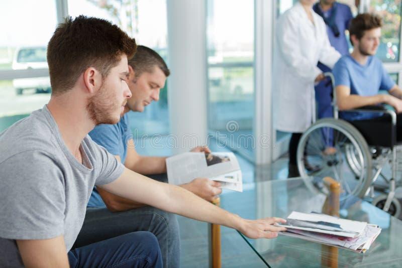 坐在候诊室医院的另外人民 库存图片