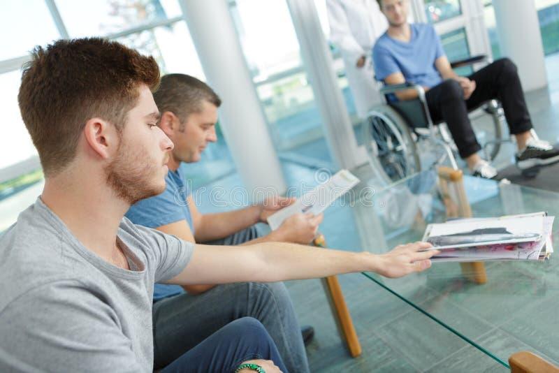 坐在候诊室医院的另外人民 免版税库存照片
