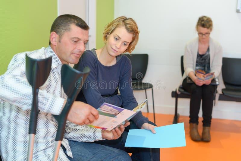 坐在候诊室医院的夫妇 免版税库存图片