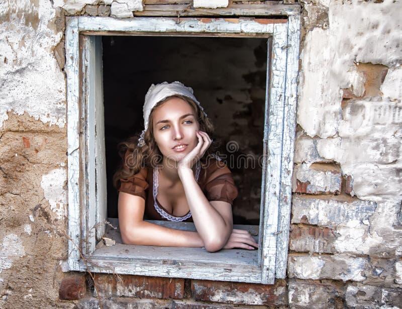 坐在偏僻老房子的感受的窗口附近的一件土气礼服的哀伤的妇女 灰姑娘样式 库存照片