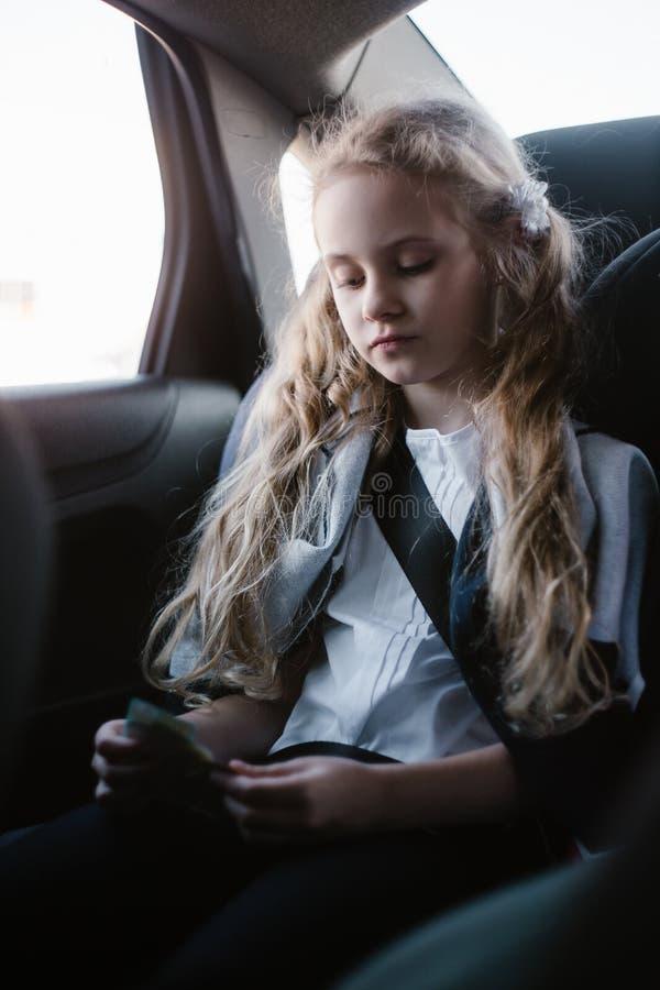 坐在儿童汽车座椅的七年迷人的女孩 免版税图库摄影