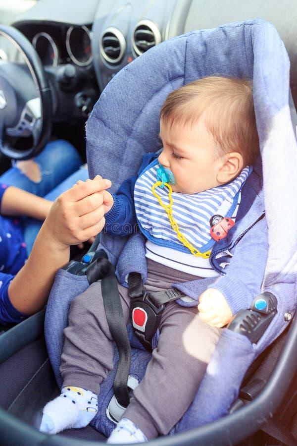 坐在儿童汽车座椅的男婴 母亲和孩子汽车的 驾驶概念的安全 图库摄影
