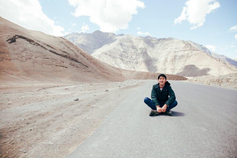 坐在充满自由和喜悦的空的路中间的年轻亚裔男性旅客在Leh,拉达克,印度 免版税图库摄影
