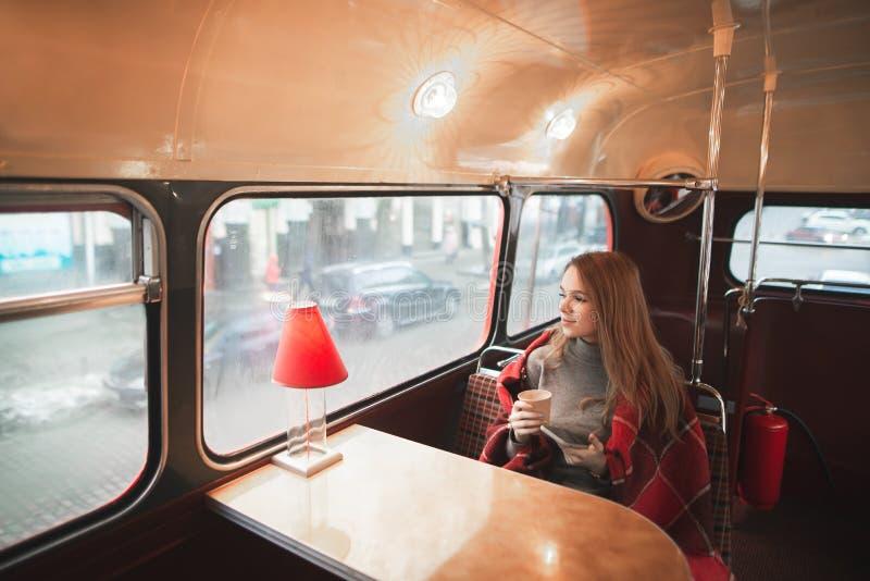 坐在公共汽车咖啡馆的桌上的年轻可爱的妇女用毯子盖 免版税图库摄影
