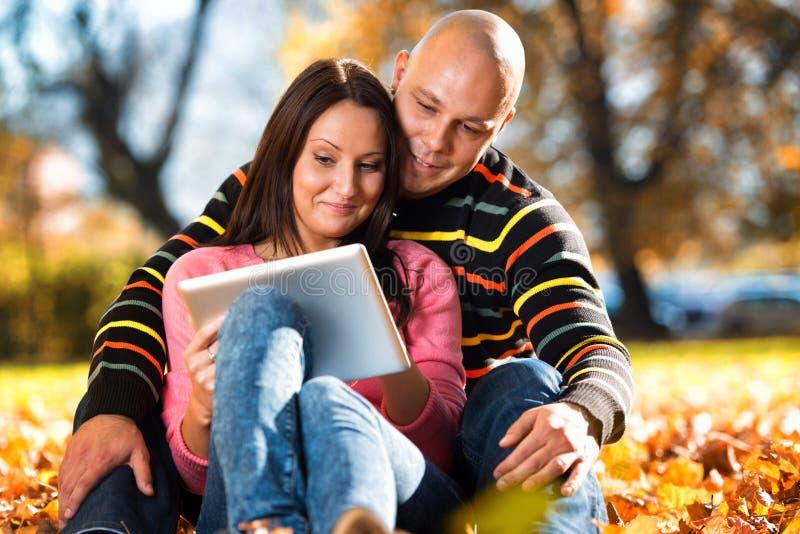 坐在公园和使用片剂计算机的美好的夫妇 免版税库存照片