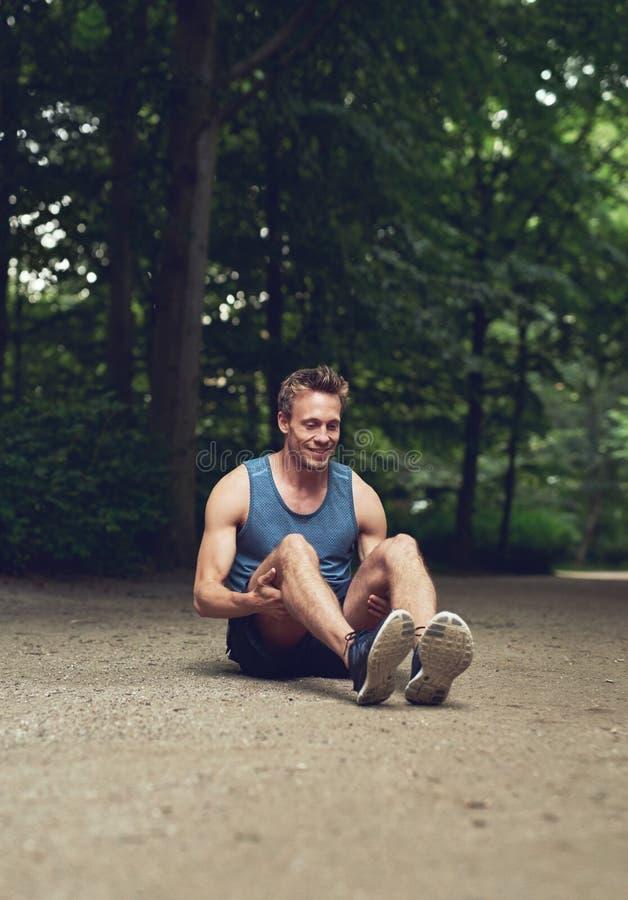 坐在公园和屈曲他的腿的适合的人 库存图片