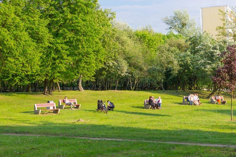 坐在公园的人们 免版税库存图片