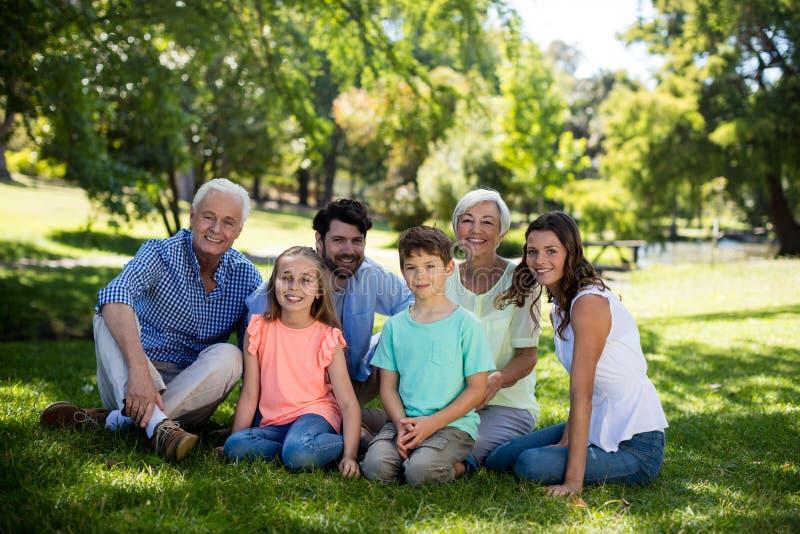 坐在公园的多一代家庭 库存照片
