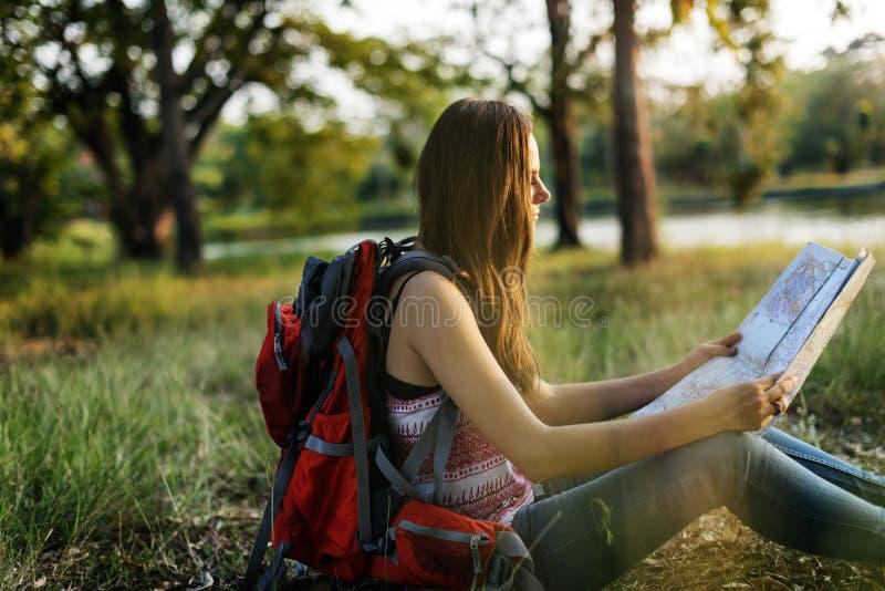 坐在公园的妇女旅行家室外 库存照片