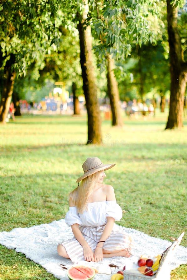 坐在公园的帽子的年轻aucasian妇女在格子花呢披肩在果子附近,草在背景中 免版税图库摄影