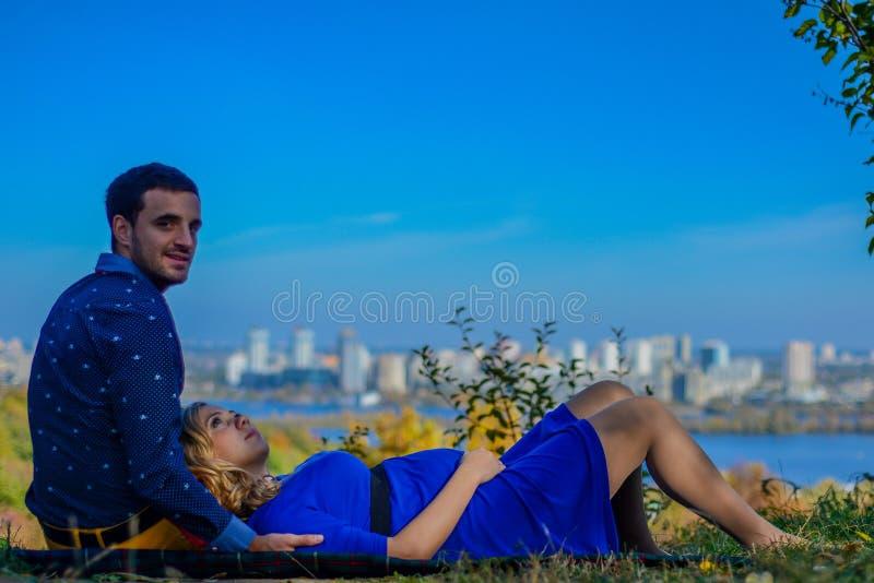 坐在公园的怀孕的夫妇有城市视图 免版税库存图片