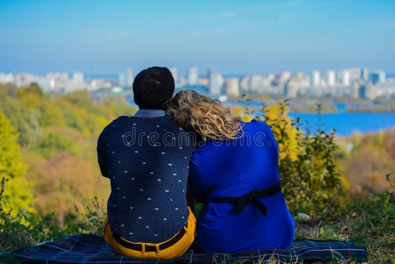 坐在公园的怀孕的夫妇有城市视图 图库摄影