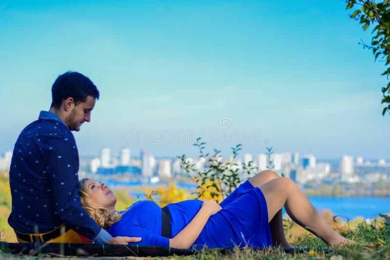 坐在公园的怀孕的夫妇有城市视图 库存图片