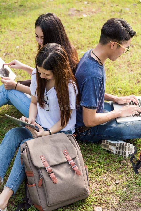 坐在公园的愉快的小组朋友学生在大学 免版税库存照片