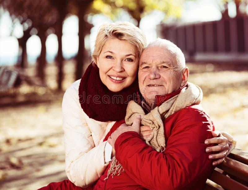 坐在公园的成熟夫妇 免版税库存照片