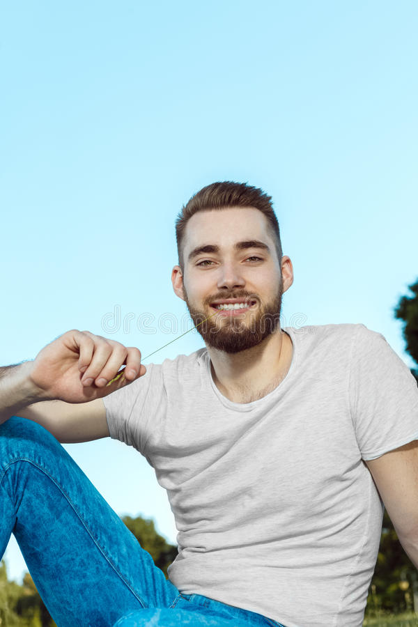 坐在公园的英俊的年轻人 免版税库存照片