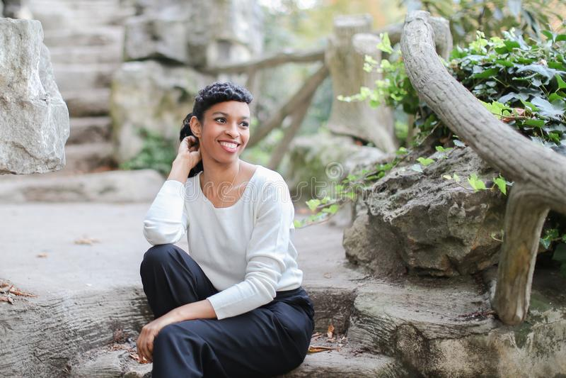坐在公园的黑人少妇在石台阶、佩带的白色女衬衫和裤子附近 免版税图库摄影