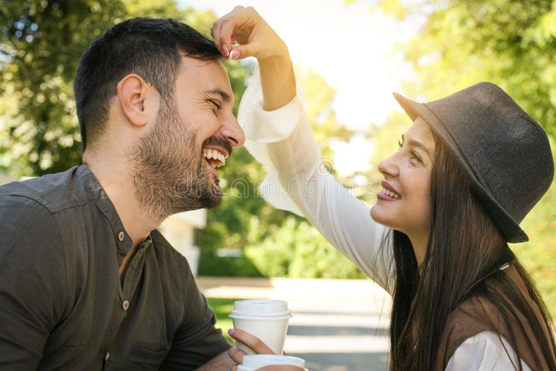 坐在公园饮用的咖啡的愉快的年轻夫妇 图库摄影