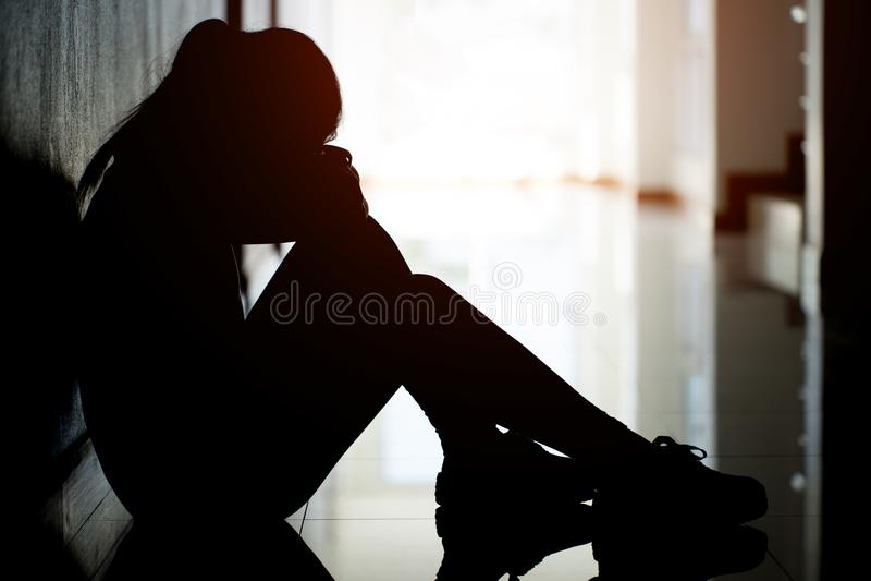 坐在公寓或办公室走道的哀伤和沮丧的妇女剪影  库存照片
