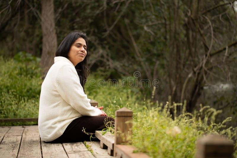坐在冥想风景的森林蜜饯的木平台的妇女 图库摄影